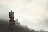 surreal man with telescope looks at infinity from the top of a stack of books in the outdoors