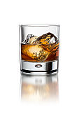 Glass with whiskey on the white background with ice