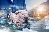 Double exposure of businessman handshake with stack of coins and city night background, money or revenue of saving and invest concept