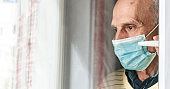 old man in sterile face mask stands near white window