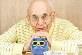old man looks straight covering blue piggy bank slot