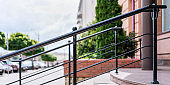 black iron railing on staircase with marble steps near hotel entrance at city street