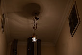 electrical light bulb hangs on long cable in toilet room of cheap hostel