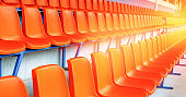 rows of empty orange stadium seats