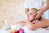 Beautiful young attractive Caucasian woman having head massage by Thai Masseur in spa salon. Beauty treatment and body care lifestyle concept