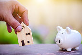 White piggy bank with wooden house model, money saving or investing for home lone or real estate concept