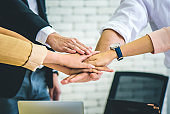 Business people standing with their hands together in modern office while meeting, celebrating victory,Team Teamwork Togetherness Collaboration Concept