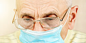 elderly man in glasses and blue disposable face mask closeup