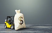 Yellow forklift carries a dollar money bag. Tax payment. Payment of taxes. Big contract, profitable deposit, take a loan. Wealth, investments in economy. financial aid. Inflation, price increases