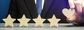 A man points to a heart instead of a fifth star. Loyalty and customer choice. The evaluation of visitors. Quality level, good service. Best customer rating. Feedback. Rating of hotels and restaurants.