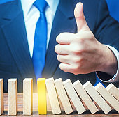 A businessman shows a thumbs up approval over a stopped process falling domino. Achieving success and completing a task. Solution. Cyber protection. Find a way stop the problem and prevent its spread.