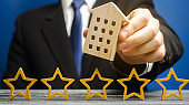 Five stars and a wooden house in the hands of a businessman. The concept of the best housing, luxury apartments VIP class. The best service. Feedback. Customer satisfaction. Hotel Rating