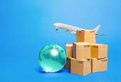 Blue globe, cardboard boxes and freight airplane. International world trade. Deliver goods, shipping. Import export freight traffic. Markets globalization. Using air transport to reduce delivery time.