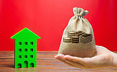Money bag and wooden house. Real estate concept. Business and finance. Savings on the purchase of housing and apartments. Mortgage, loan, taxes, debts. Family home budget. Building maintenance