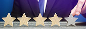 Businessman points to the fifth star. The concept of the rating of hotels and restaurants. The evaluation of visitors. Quality level, good service. Best customer rating. Feedback. Satisfaction. Banner
