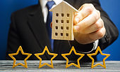 Four stars and a wooden house in the hands of a businessman. The concept of a hotel or housing rating. Good quality service. Review critic and visitors. Feedback.