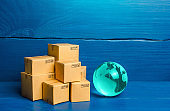 Planet Earth globe and boxes. Global business and world trade. Distribution of goods, import and export of products. Freight shipping delivery to new markets. International trade and transportation.