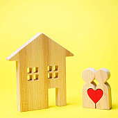 A couple of lovers is standing near the wooden house. Valentine's Day. Affordable housing for young families. Rental Property. Mortgage and loan. The concept of finding an apartment or home