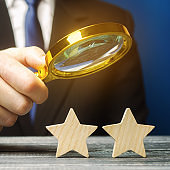 A critic holds a magnifying glass over two stars. Rating, feedback and review of a restaurant or hotel. Quality of service. Evaluation of visitors