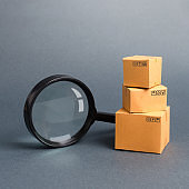 Cardboard boxes and a magnifying glass. Warehouse of finished products and equipment. buying and selling goods and services, internet commerce, online shopping, trade and turnover. Import and export