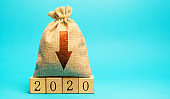 Money bag with down arrow and wooden blocks 2020. Economic crisis and recession. Bankruptcy and financial crisis. Analysis and analytics. Results of the year
