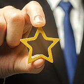 Man holds a golden star in his hand. Symbol of success and excellence. Good reputation, prestige, high recognition. Status, rating. Good ratings and reviews. VIP. Job promotion and career growth.