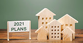 A poster with the words Plans 2021 and wooden houses. Real estate planning and financing concept. Housing market. Mortgage, loan, investment. Repairs and refinance home. Forecasts