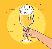 hand holding a beer cup glass, on yellow background