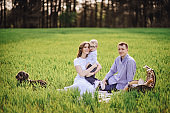 Family on a picnic in the forest. In the meadow. Picnic basket with food. The dog runs and wants to play. A child with glasses. Blue color in clothes. To eat outdoors. Time with family.