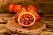 Cutting board with halved sicilian oranges on a wooden table