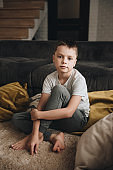 Family in a big house. Lifestyle Home comfort. Children at home. Children playing on the floor. Textile. The boy is sitting on the floor. Brown sofa, yellow pillows. Portrait of a child.