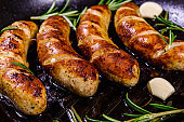 Roasted sausages with rosemary twigs and garlic in a cast iron grill pan