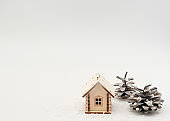 Wooden house in snow with pine cones like decorated Christmas tree on white background. Staying at home during Christmas, New Year  holidays concept. Isolation and coronavirus pandemic. Winter card.