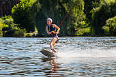 Woman riding wakeboard. Ð¡uts waves and raises splash in a summer lake