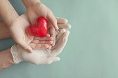 Doctor hands with medical gloves holding child hands and red heart, health insurance and donation concept