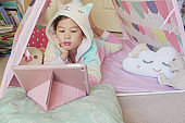 Mixed race Asian girl making facetime video calling with tablet at home, using  learning online app, social distancing, isolation, homeschooling education, learning remotely concept