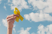 Hands holding yellow gold ribbon over blue sky, Sarcoma Awareness, Bone cancer, childhood cancer awareness, September yellow, World Suicide Prevention Day concept