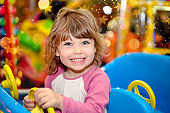 cute little girl in a children's carousel