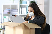 Fired executive with mask crying packing her stuff