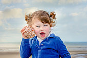 cute little girl listening to the sea in a seashell