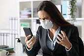Angry executive with mask reading news on phone