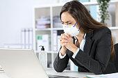 Executive wearing mask praying at the office