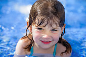 portrait of a cute little girl playing in the pool on vacation