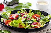 Vegetable salad of spinach, tomato, lettuce and cucumber.