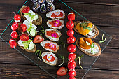 Snack tray on woody background: rolls, canapes, rolls, stuffed tomatoes, sandwich with caviar. Top view