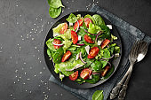 Top view of a fresh green vegetable salad of spinach, tomato, lettuce and sesame seeds.