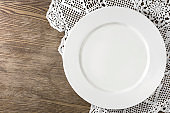 Empty white plate served on old style wooden table with handmade tablecloth. Top view