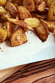 Part of white paper and cutting board with delicious baked golden potatoes slices with seasoning from sideways close up. On wooden table with free space for text