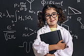 little scientist in lab coat with a notebook