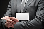 white blank business card closeup in businessman hand, gray suit, dark wall background